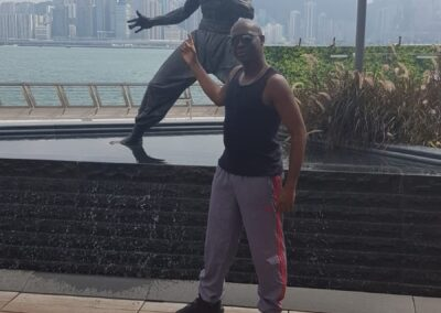 Sifu Ryan posing in front of Bruce Lee whilst training in Hong Kong